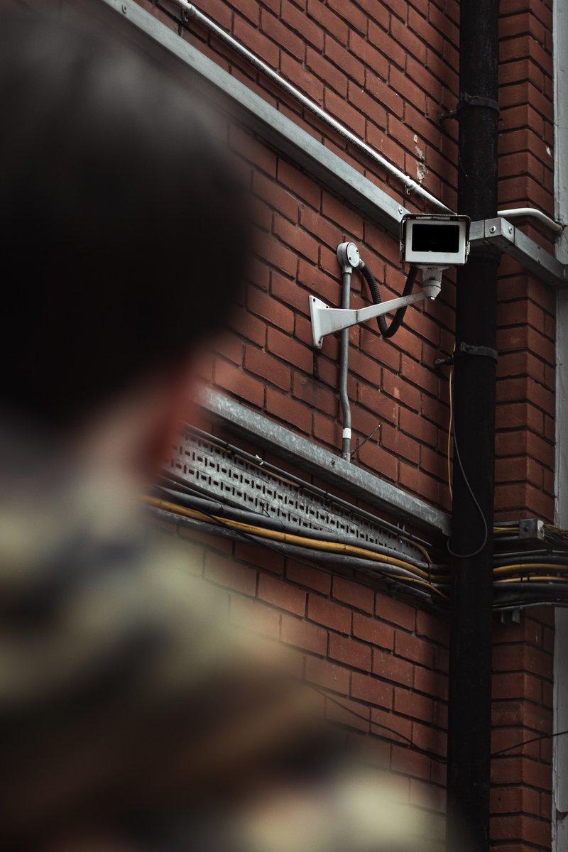 Person betrachtet Überwachungskamera. Zum Thema Internet-Sicherheit